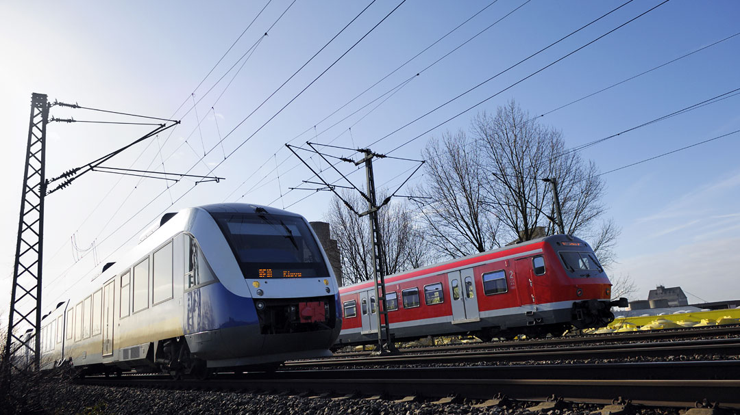 Blauer und ein roter fahrender Zug mit blauen Himmel
