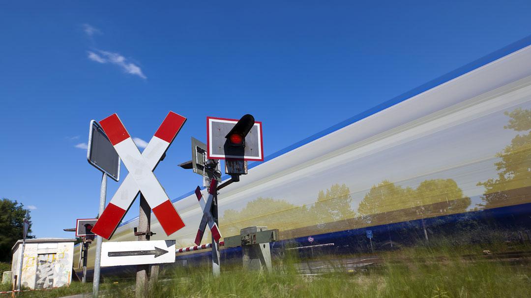 Bahnübergang mit Schranke und fahrenden Zug
