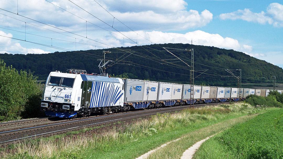 fahrender Zug mit vielen Güterwaggons in Sommerlandschaft