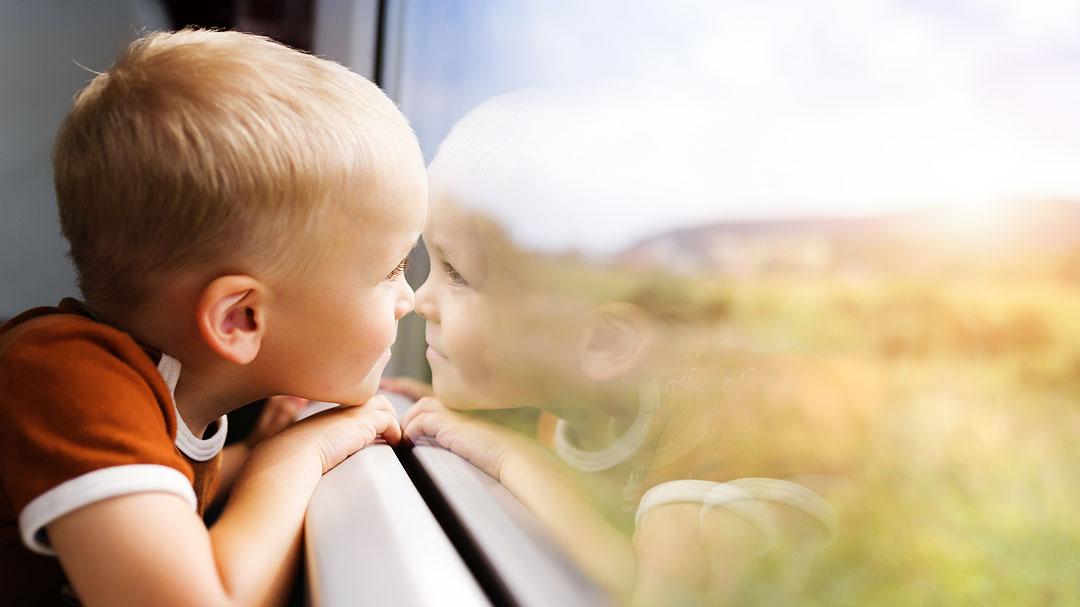 Junge schaut aus Zugfenster