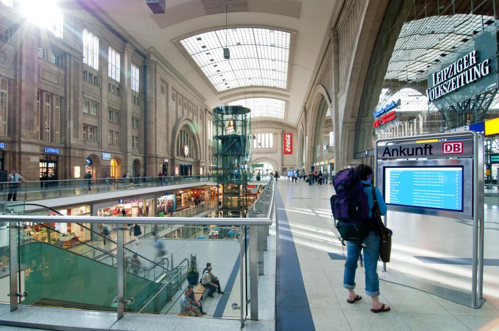 Bahnhofshalle mit Person vor einem Bildschirm