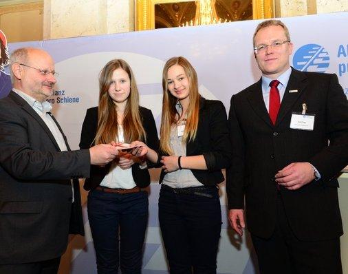 Jurymitglied Alexander Kirchner (EVG) überreicht Saskia und Annabell einen Reise-Gutschein für einen Städtetrip nach Köln - zu Peter Gitzen und dessen Familie.