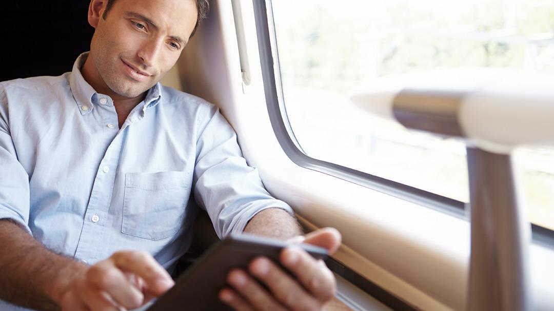 Mann liest im Zug am tablet