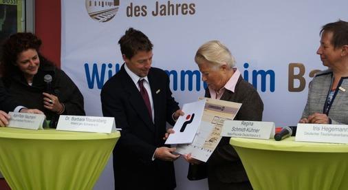 Gerti Heupel erhält vom Verband der Bahnhofsbuchhändler, vertreten durch Michael Ganter, einen Buchgutschein im Wert von 100 Euro.