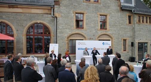 80 Ehrengäste feiern vor dem Bahnhof Oberursel die Enthüllung der Siegerplakette