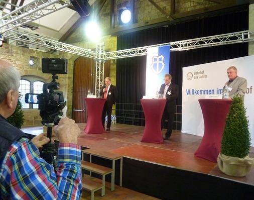 Auf der Bühne Allianz pro Schiene-Geschäftsführer Dirk Flege und die Juroren Karl-Peter Naumann sowie Dieter Harms