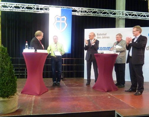 Jurymitglied Karl-Peter Naumann überreicht Bahnhofsmanager Gerd Tucholka die Urkunde
