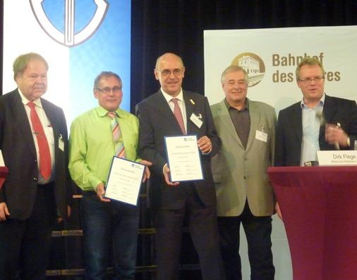 Die stolzen Sieger, Bahnhofsmanager Gerd Tucholka und Bürgermeister Stefan Schwenk, zeigen ihre Urkunden