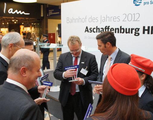 Podiumsgäste inklusive Jury-Mitglied Dirk Flege erhalten Stationsschilder geschenkt