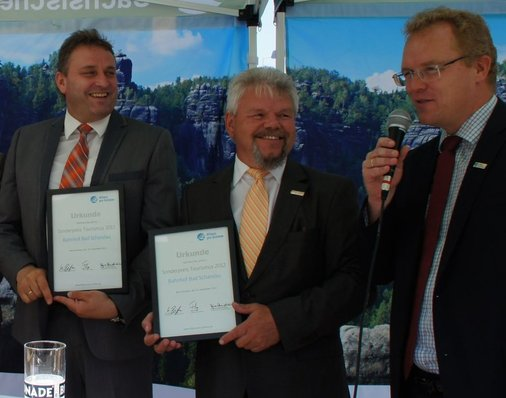 Dirk Flege überreicht die Urkunden im Namen der Jury an Heiko Klaffenbach, DB Bahnhofsmanager und an Bad Schandaus Bürgermeister Andreas Eggert.