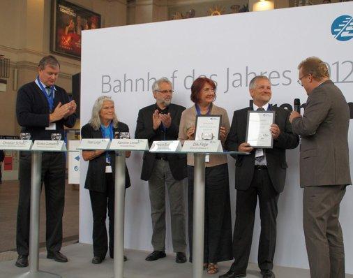 Dirk Flege übergibt je eine Auszeichnung an den Bürgermeister und an den Bahnhofsmanager.