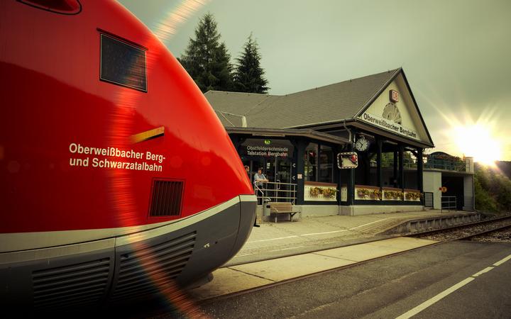 Ein Zug der Schwarzatalbahn steht vor dem Bahnhof Obstfelderschmiede in der Abendsonne.