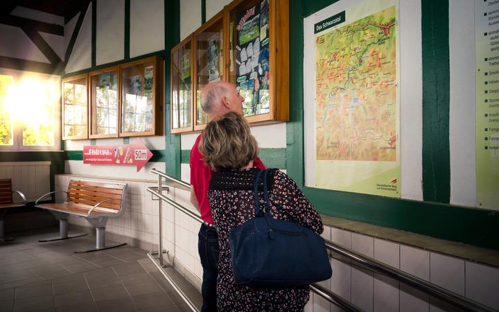 Touristen vor einer Karte im Bahnhofsgebäude