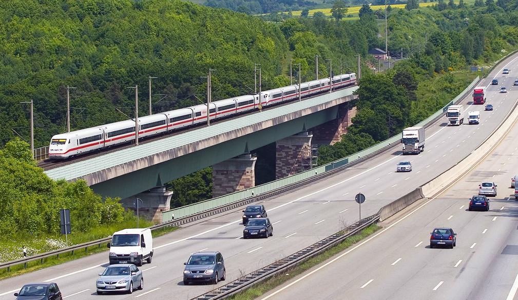 Schnellzug fährt über eine Brücke, im Hintergrund Bäume und Rapsfeld, davor eine Autobahn - Flächenverbrauch