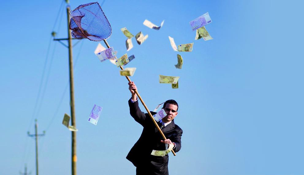 Mann fängt Geldscheine mit einem Netz