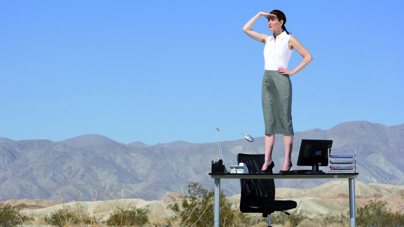 Businesswoman standing on desk in desert, hand on hip, looking i