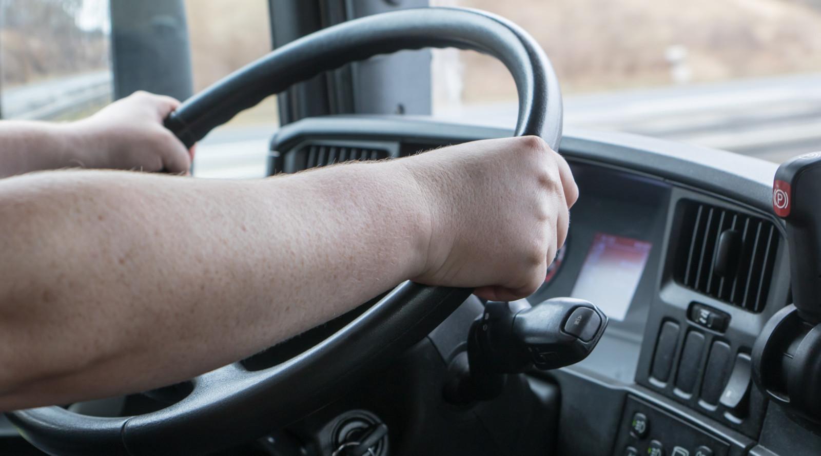 Zwei Hände umfassen das Lenkrad eines Lkw