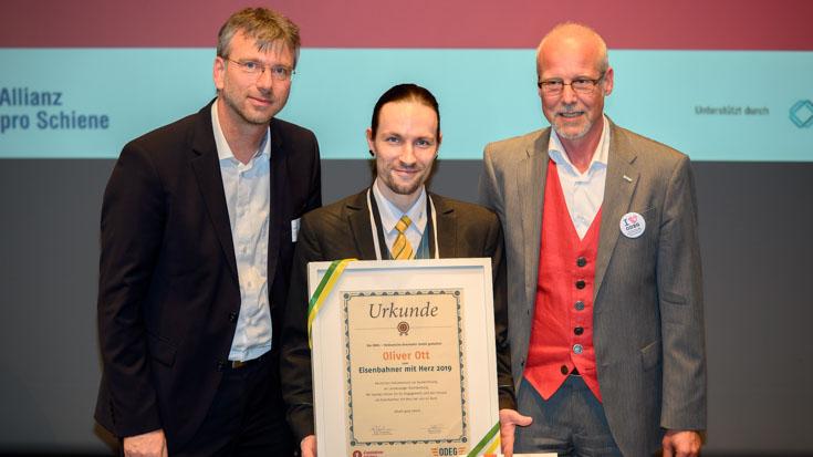 Brandenburgs Landessieger Oliver Ott freut sich mit Jury-Mitglied Frank Zerban (links) und Arnulf Schuchmann (Sprecher der Geschäftsführung ODEG)