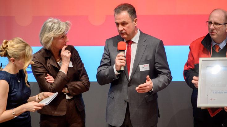 GDL-Chef Claus Weselsky würdigt Sondersieger Thomas Wiese (rechts), Zugbegleiter von National Express. Einsenderin Inge Schürmann und Moderatorin Janine Mehner hören zu.