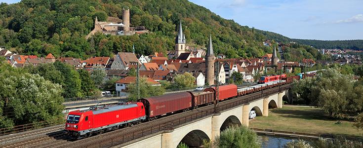 Eine Güterbahn vor idyllischer Kulisse.